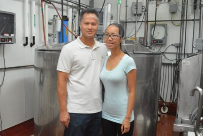 Fred and Phuong Chen are pictures in front of dairy production equipment